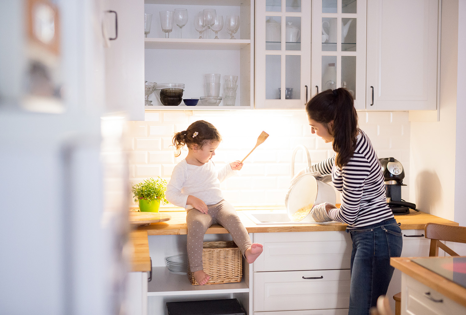 Mother and daughter making pasta in kitchen